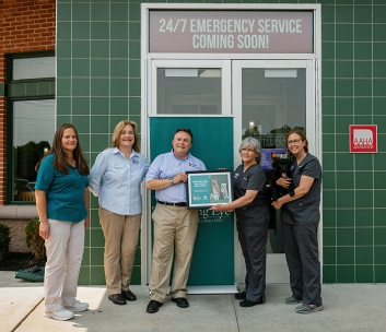 Seeing Eye President Glenn Hoagland stands with Absecon Veterinary staff in front of the clinic's front entrance. They are all smiling as Glenn hands one of the staff members of framed photo of Seeing Eye dogs and puppies.