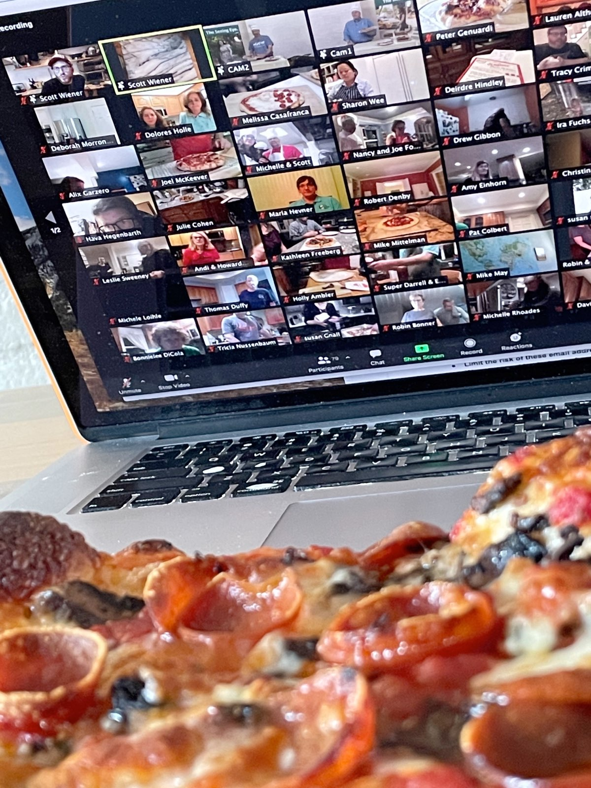 A close-up image of a freshly baked pizza resting before a computer screen showing a zoom call in progress with a full grid of participants.