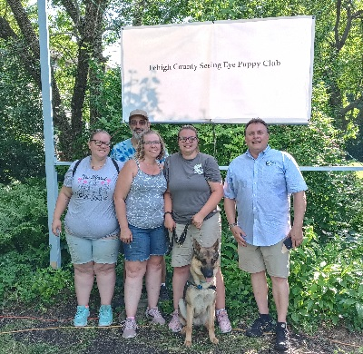 """Glenn Hoagland stands with a father and his three daughters with their German shepherd puppy. Above them a sign reads """"Lehigh County Seeing Eye Puppy Club"""""""
