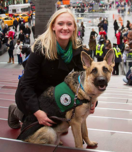 A puppy raiser smiles beside a German shepherd with the busy streets of Times Square in the background. The dog is full grown and will return for training soon.