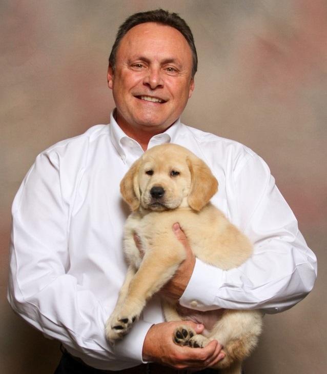 Glenn Hoagland, holding a yellow Labrador/golden retriever cross puppy.