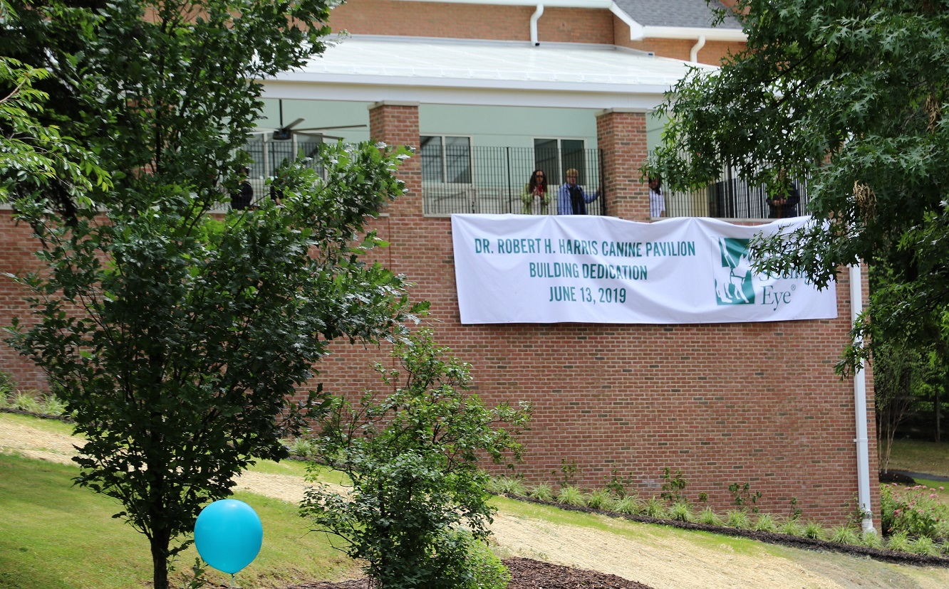 "The brand new pavilion stands tall and proud on a grass-covered hill. Draped across the front of the building covering the building's name is a white banner that reads in green letters, ""Dr. Robert H. Harris Canine Pavilion Building Dedication, June 13th, 2019"". Leafy green trees stand on either side of the building, and a teal-colored balloon stamps the bottom left corner of the photo."