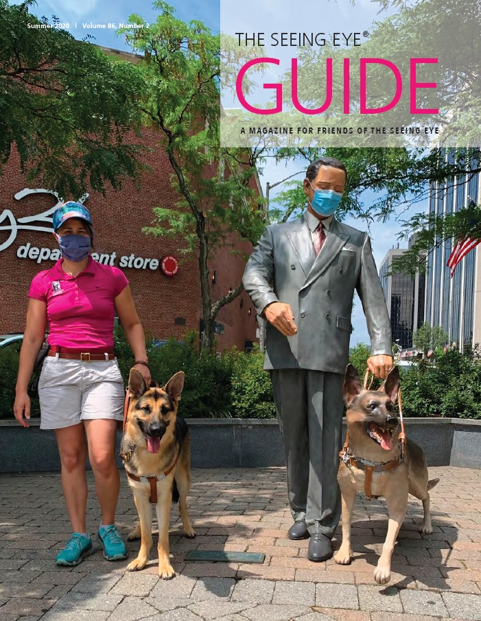 The cover of The Guide Summer 2020 shows Seeing Eye Instructor Nicole Murray with a German shepherd standing next to the statue of Morris Frank and Buddy. Nicole and the statue of Morris are both wearing masks!