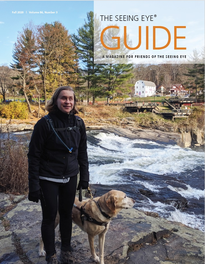 The cover of The Guide Fall 2020 shows Seeing Eye graduate Catherine Getchell with a yellow Labrador/golden retriever cross standing next to a rushing river.
