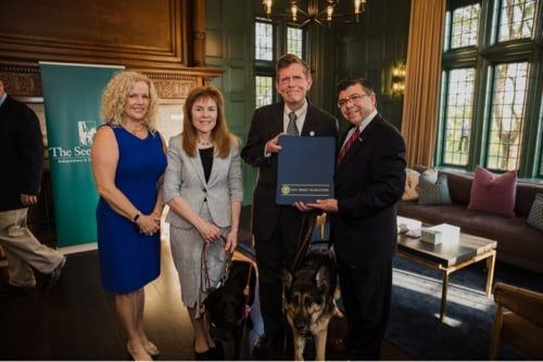 Amy Bucco, Ginger Kutsch, Seeing Eye President & CEO Jim Kutsch and Assemblyman Anthony Bucco pose for a photo with the three proclamations from the state of New Jersey. Ginger's black Lab and Jim's German shepherd stand beside them.