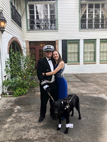 Robert in his dress uniform, hugs his new bride, Kirstiana. She's wearing a royal blue gown. Robert's black Lab, Jackson, is beside him, wearing a bow tie and tuxedo cuffs on his front paws.